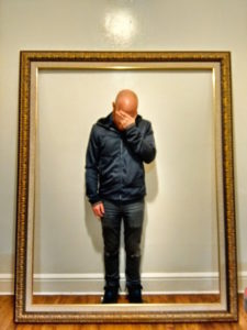 Photograph of a man facepalming himself surrounded by a gilded frame