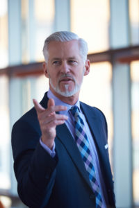 Photo of senior businessperson with grey beard and hair in a decisive stance