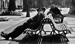 Photo of men sleeping while sitting on public benches.