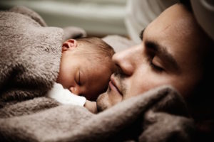 Photo of baby cuddling with father.