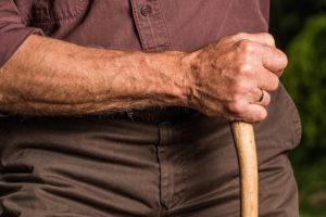 Photo of an elderly man holding a walking stick