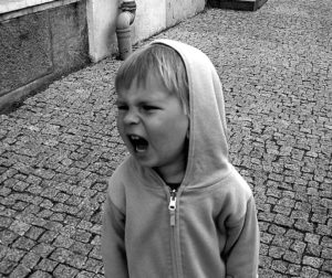 Photo of little boy screaming and shouting with an angry face.