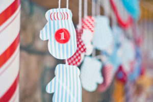 Christmas Advent Calendar Mittens hanging by a fireplace