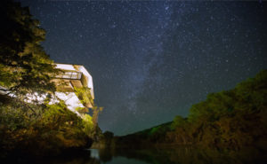 Photo of Laity Lodge lit up at night with a starry night sky.