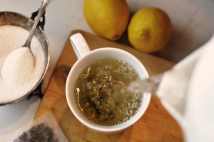 Image of tea being poured with sugar and lemons available.