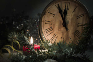 An old faced clock lit by candlelight surrounded by Christmas greenery.