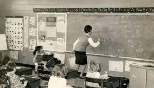 Teacher writing Hebrew on a chalkboard
