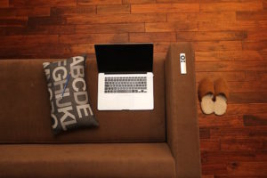 At home with a laptop on a couch with cushion and slippers.