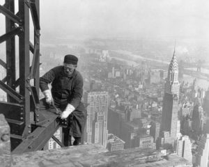 Black & white photo of man working on a skyscraper