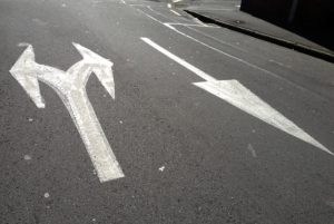 Arrows going in different directions, painted on the street.