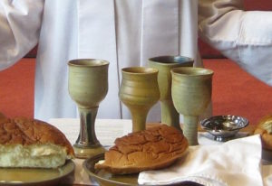 Communion table set with 4 cups with a broken loaf of bread.