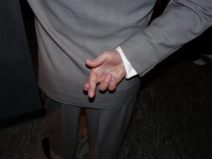 Business man with his fingers crossed behind his back.