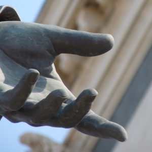 Photo of the hand of a statue extended, palm up, as if in offering.