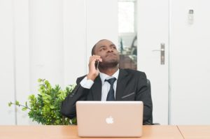 A business man on a phone call seemingly not liking what he hears.