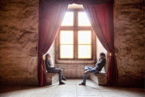 Two people sitting across from one another in an alcove as if in conversation.
