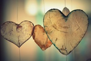 Wooden pieces in the shape of hearts hung vertically.