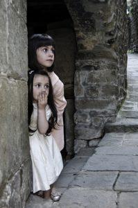 Girls peeking around the corner in surprise.