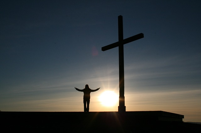 Sunrise silhouette of a person standing with arms out next to a cross.