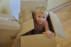 Little boy playing in/with a cardboard box.