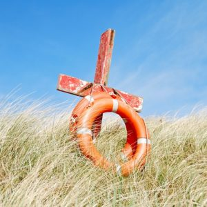 A cross and life preserver on a beachside hill.