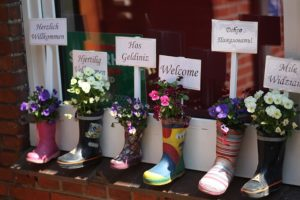 Flowers planted in rain boots with welcome signs in different languages.