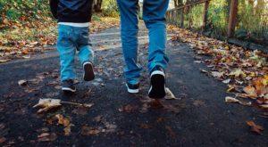 A child dressed similarly to dad, walks alongside him.