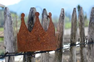 A rustic crown on a wooden fence.