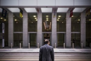 A person in a suit getting ready to enter a business building.