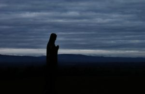 Silhouette of morning or evening prayer with a background of hills and a sky filled with clouds.