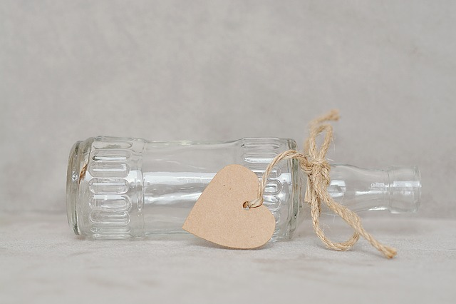 An empty bottle tipped over with a heart tied around it