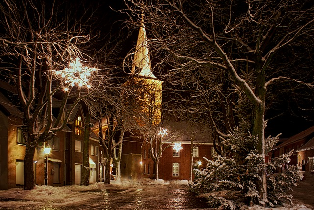 A quiet street with a church peacefully lit at night.