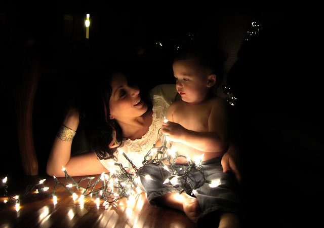 A mother and child lit by a string of Christmas lights