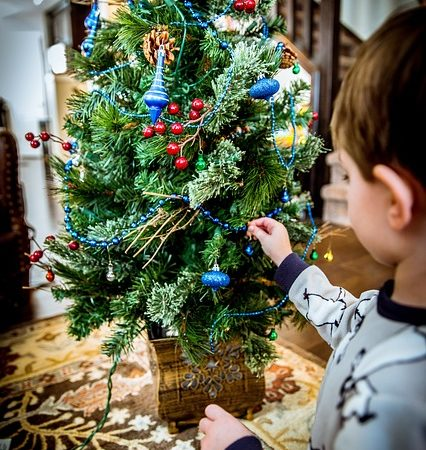 A child decorating a Christmas tree.