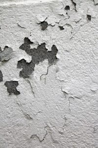 Cracked and peeling paint on a wall.