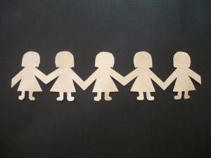 Female paper dolls, hand-in-hand.