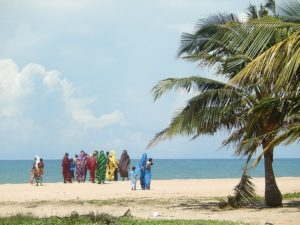 Women wrapped in colorful fabrics, walking on the beach in the distance.