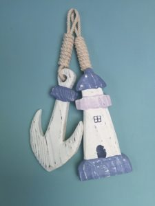 Wooden hangings of an achor and a lighthouse.
