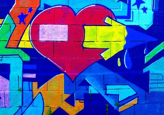 Graffiti art of a heart with a directional arrow among other paths.