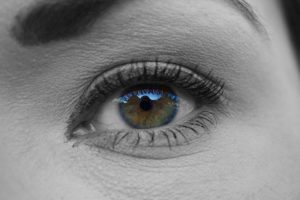 A sepia colored photo close-up of a person's eye, with only color in the iris.