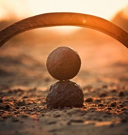 Round rocks balanced on one another under an arc highlighted by the sun shining through.