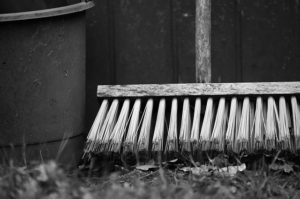 A black and white photo of a bucket and broom laid against the fence in a hard.