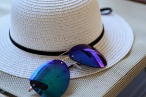 A hat and reflective sunglasses laid out.