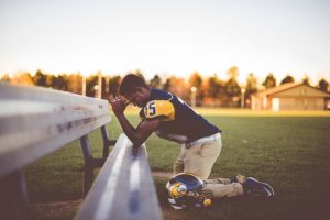 An American football player kneeling in prayer on a field bench.