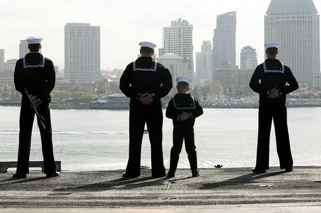 A child dressed in a sailor's uniform standing next to Navy seamen.