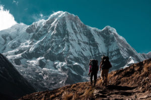 Two people hiking up a tall mountain.