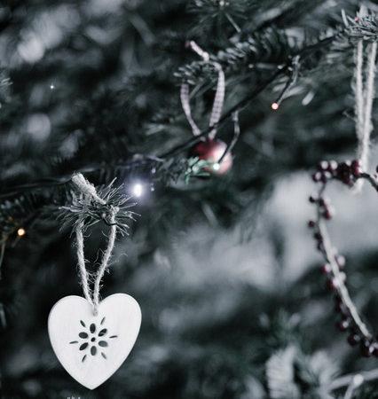 A heart shaped ornament hung on a Christmas tree.