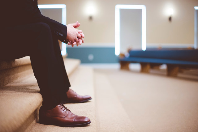A person waiting at the front of an empty church sanctuary as if forgotten.