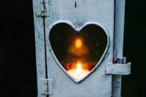 A lit flame in a heart shaped window.