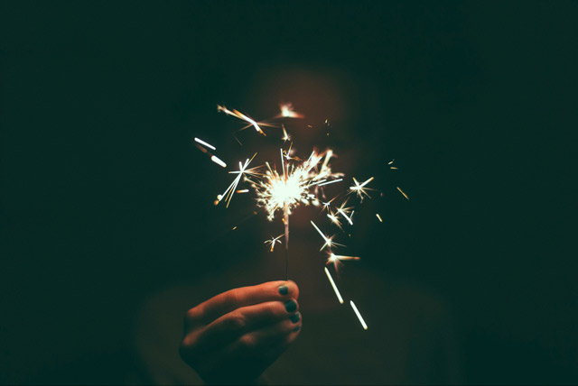 A person holds up a sparkler lighting up the dark.