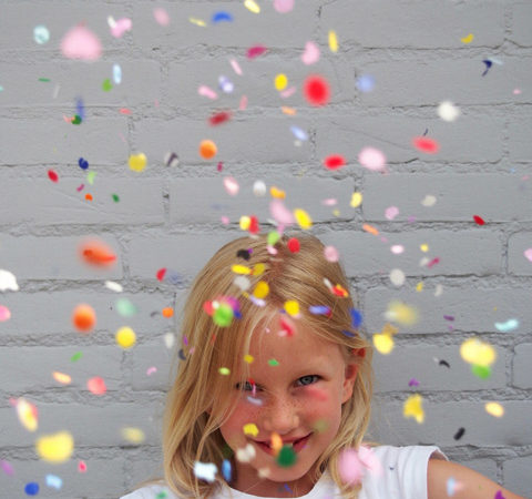 A child in the middle of colorful confetti tossed into the air.